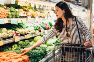 Woman In Supermarket Pushing Shopping Cart