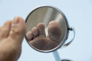Person Looking At The Sole Of The Foot In A Mirror.